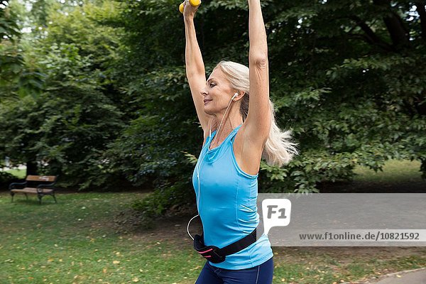 Mature woman lifting hand weights whilst training in park