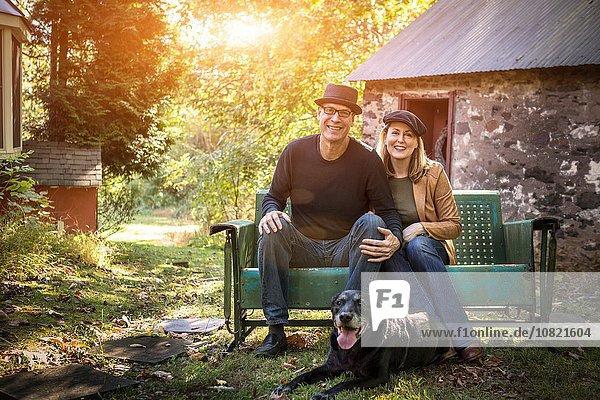Porträt eines reifen Paares mit Hund  auf der Bank sitzend  im Freien
