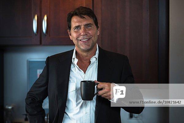 Reifer Mann im Hemd und Anzug mit Kaffeetasse und lächelndem Blick auf die Kamera.