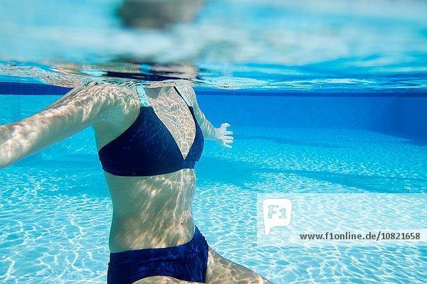 Unterwasseransicht der jungen Frau im Schwimmbad  Nacken im Bikini
