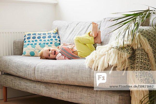 Porträt eines Kleinkindes auf dem Sofa im Wohnzimmer