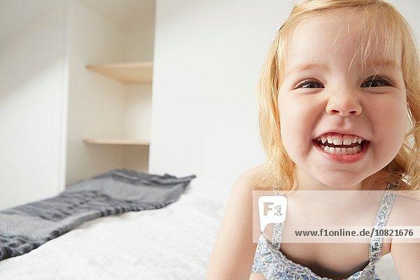 Nahaufnahme des weiblichen Kleinkindes beim Spielen auf dem Bett