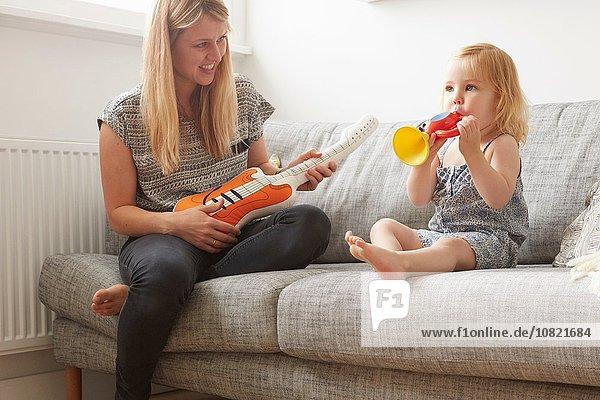 Kleinkind und Mutter spielen mit Spielzeug Trompete und Gitarre auf Sofa