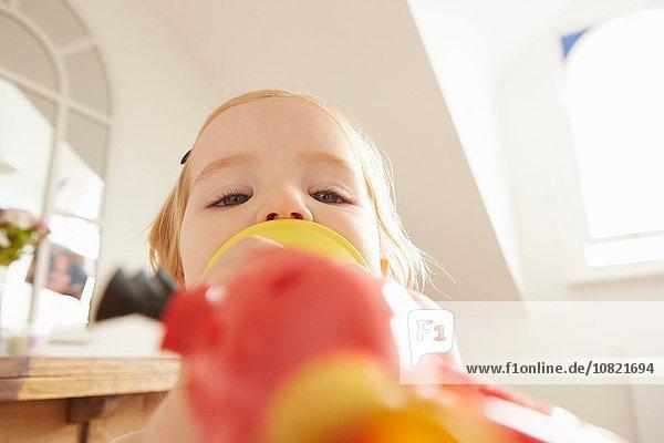 Nahaufnahme des weiblichen Kleinkindes beim Spielzeugtrompetenspiel
