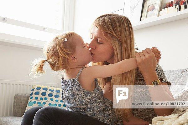Mittlere erwachsene Frau küssend Kleinkind Tochter auf Sofa