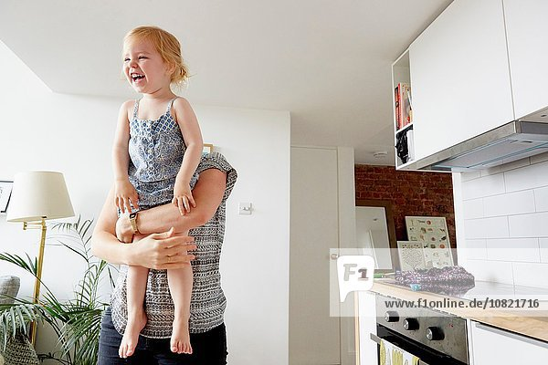 Woman lifting up toddler daughter in kitchen