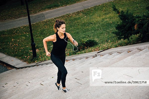 Frau rennt im Park die Treppe hinauf