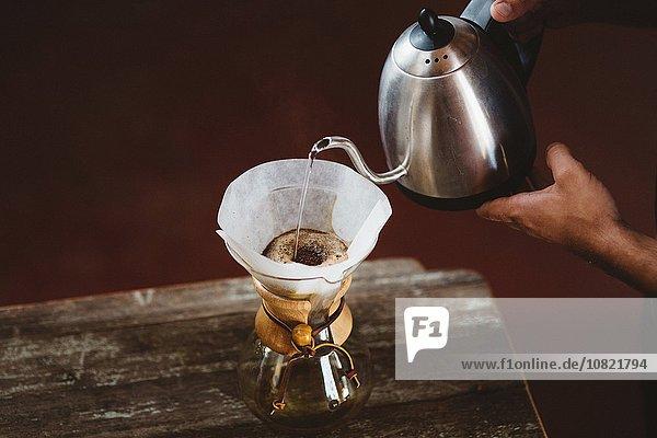 Mann gießt Wasser in die Filterkaffeemaschine
