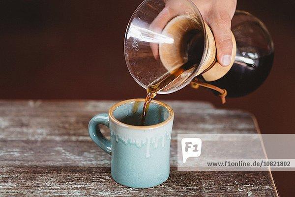 Mann gießt Kaffee aus der Filterkaffeemaschine