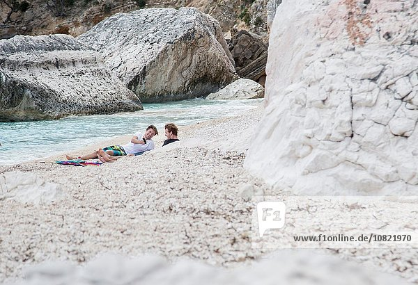 Junge Männer entspannen am felsigen Strand mit dem Smartphone  Golfo di Orosei  Sardinien  Italien