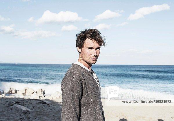 Junger Mann am Strand vor der Kamera  Costa Smeralda  Sardinien  Italien