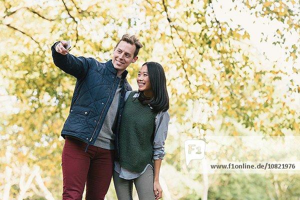 Mid adult couple taking smartphone selfie in park