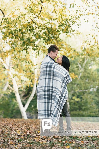Romantic mid adult couple wrapped in blanket in park