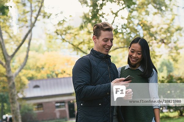 Mid adult couple in park reading smartphone texts