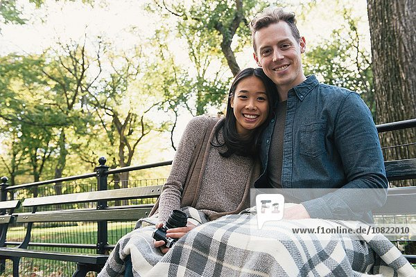 Portrait of mid adult couple sitting on park bench holding SLR camera