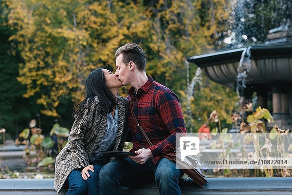 Mid adult couple kissing at Bethesda fountain in Central Park  New York  USA