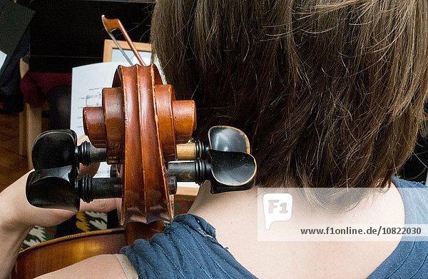 Rückansicht junge Frau junge Frauen üben Faden Cello spielen Saite