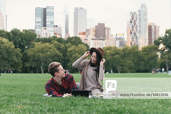 Mid adult woman trying on felt hat for boyfriend in Central Park  New York  USA