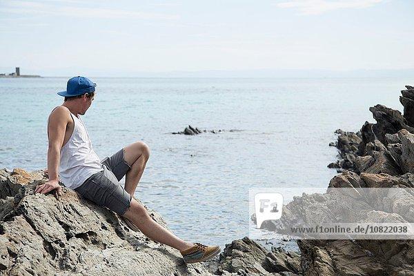 Seitenansicht des jungen Mannes auf Felsen mit Blick aufs Meer  Stintino  Sardinien  Italien
