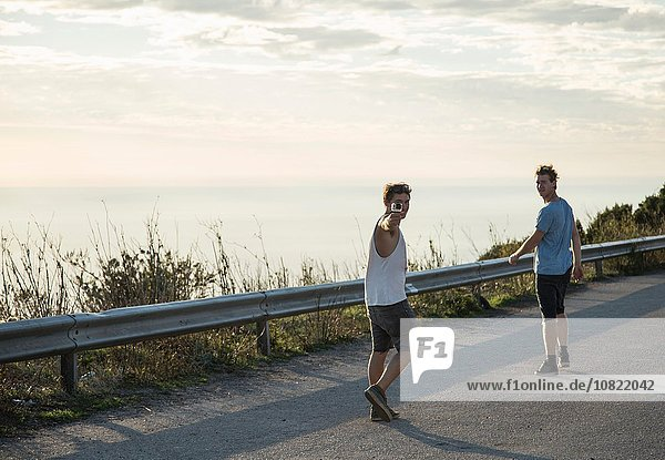 Durchgehende Rückansicht von jungen Männern auf der Straße mit Blick über die Schulter  Alghero  Sardinien  Italien