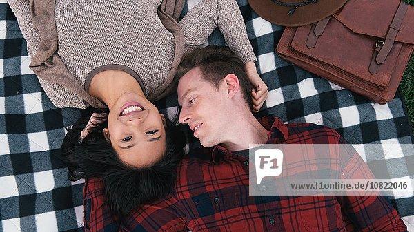 Overhead portrait of romantic mid adult couple lying on checker blanket