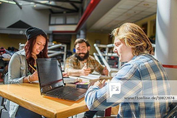 Drei erwachsene Studenten  die am Schreibtisch arbeiten.