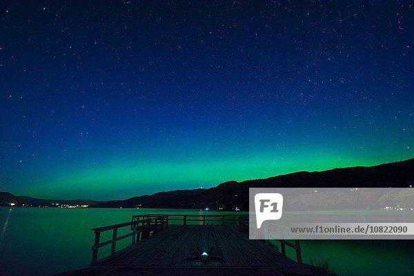 Mann  der auf dem Pier liegt und nachts starrt  Wharf Park  Naramata  British Columbia  Kanada