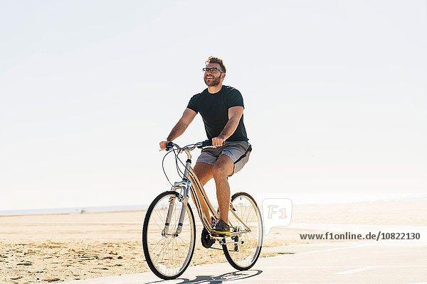 Junger Mann radelt am Strand entlang des Weges