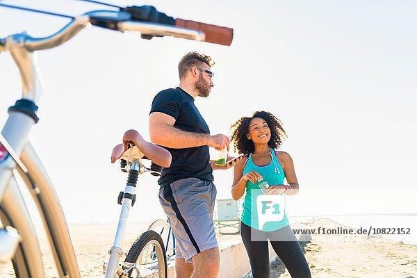 Paar  das eine Pause vom Radfahren einlegt  Flaschengetränk hält.