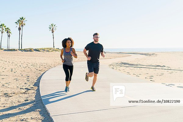 Paar läuft auf dem Weg am Strand