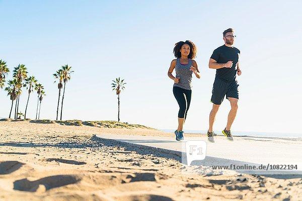 Paar  das auf dem Weg am Strand läuft  Blick in den niedrigen Winkel