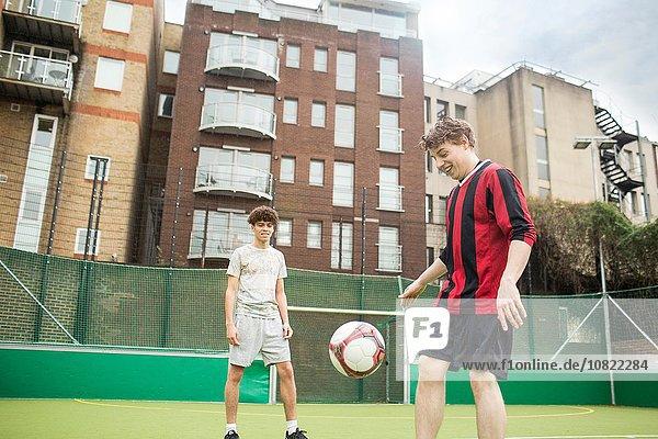 Zwei junge Männer spielen Fußball auf dem Stadtfußballplatz