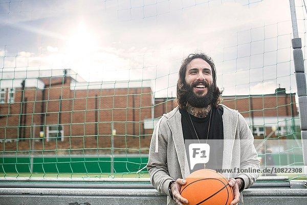 Porträt eines erwachsenen Mannes  der Basketball hält.