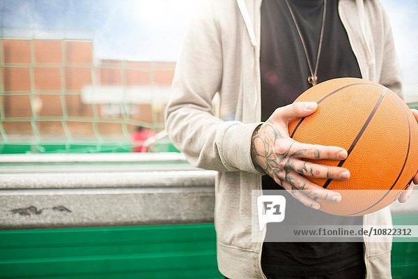 Mittlerer Erwachsener Mann mit Basketball  Mittelteil