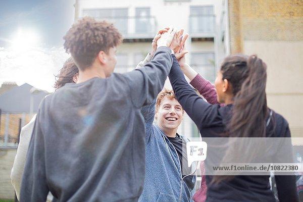 Gruppe von Erwachsenen  berührende Hände  im Freien