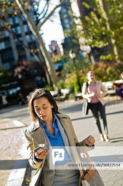 Junge Frau liest Smartphone beim Spaziergang durch den Stadtpark