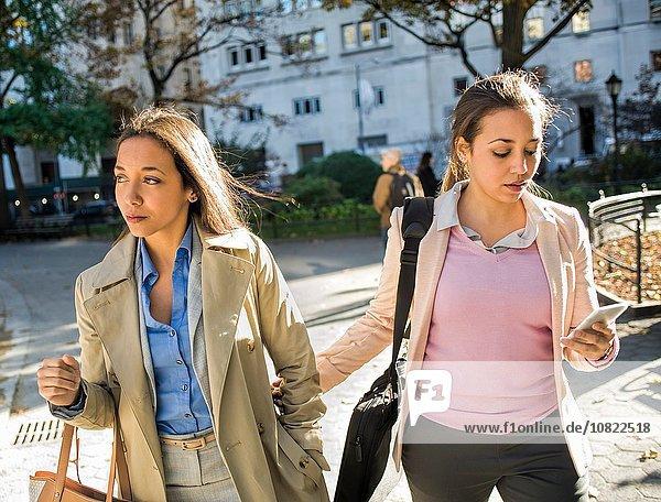 Junge erwachsene weibliche Zwillinge gehen Arm in Arm durch den Stadtpark