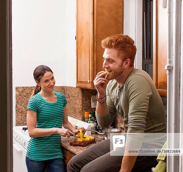 Paar in der Küche beim Zubereiten des Essens lächelnd