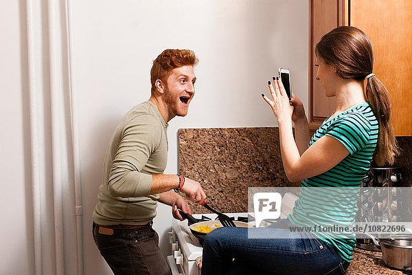 Seitenansicht der jungen Frau in der Küche mit dem Smartphone  um den jungen Mann beim Kochen zu fotografieren.