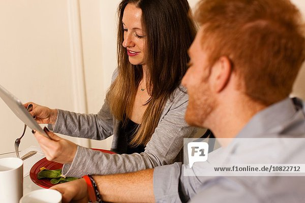Side view of couple at dining table using digital tablet smiling