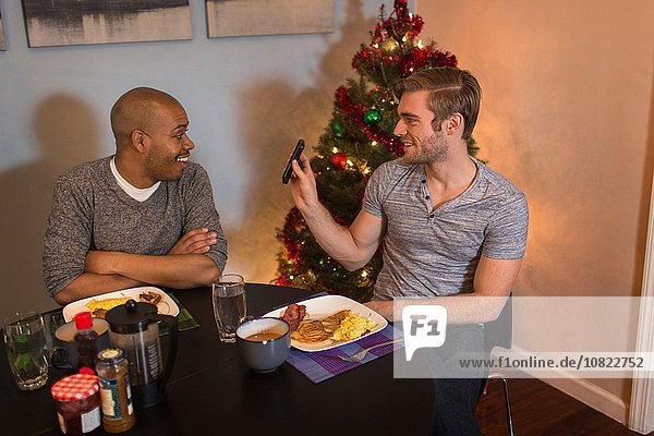 Male couple sitting at table  having breakfast  looking at smart phone  Christmas tree in background