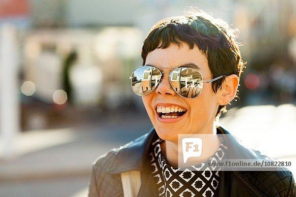 Porträt einer mittleren erwachsenen Frau  im Freien  mit verspiegelter Sonnenbrille