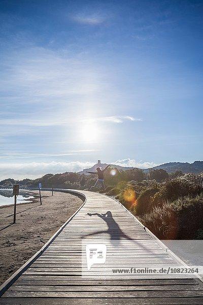 Frau springt über Strandpromenade  Villasimius  Sardinien  Italien