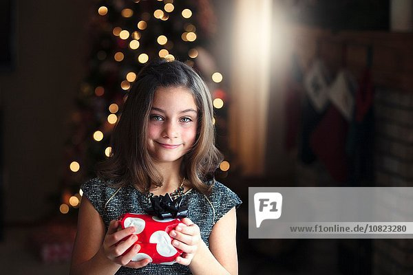 Portrait of girl in front of christmas tree holding gift looking at camera smiling