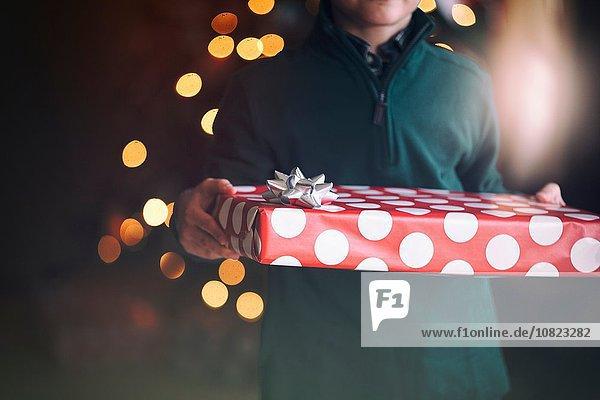 Beschnittene Ansicht des Jungen vor dem Weihnachtsbaum mit Geschenk