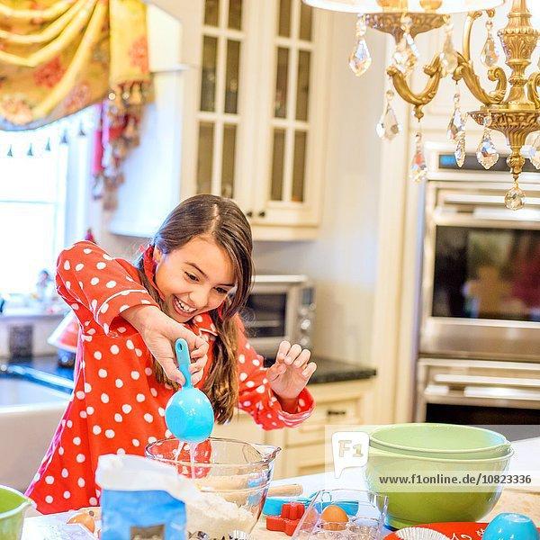 Mädchen im Pyjama an der Küchentheke mit Messlöffel lächelnd