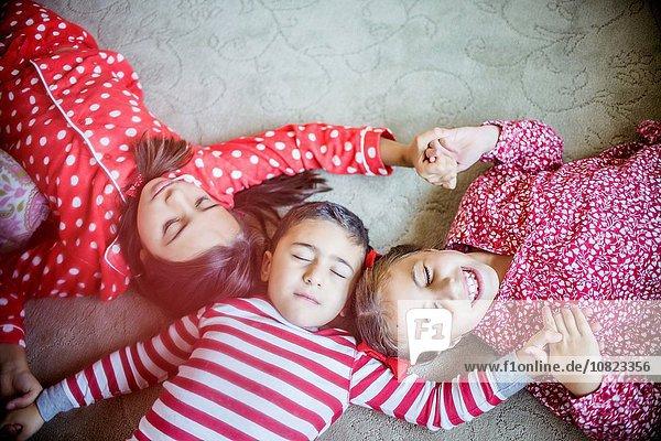 Draufsicht auf Kinder im Pyjama  die auf einem Teppich liegen und die Augen geschlossen halten.