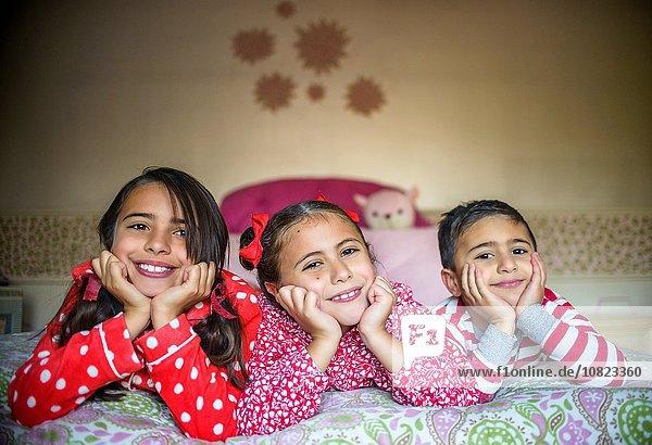 Kinder im Schlafanzug liegend auf dem Bett Kinn in den Händen und schauen lächelnd in die Kamera.