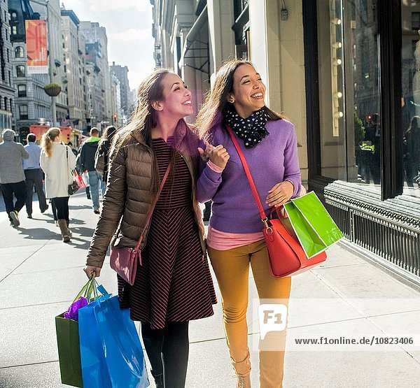 Young female adult twins carrying shopping bags strolling and chatting on city sidewalk