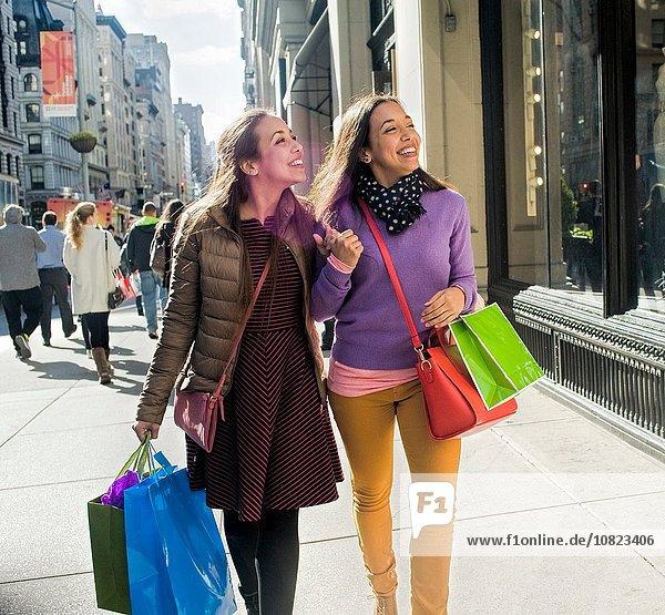 Junge erwachsene Zwillinge mit Einkaufstaschen auf dem Bürgersteig der Stadt